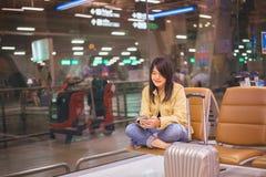 Beau voyageur asiatique de femme à l'aide du téléphone portable dans l'aéroport Photo stock