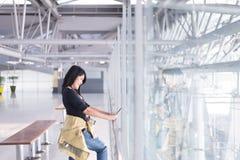 Beau voyageur asiatique de femme à l'aide du téléphone portable dans l'aéroport Photographie stock libre de droits