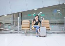 Beau voyageur asiatique de femme à l'aide du téléphone portable dans l'aéroport, mode de vie utilisant le téléphone portable Photographie stock libre de droits