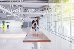 Beau voyageur asiatique de femme à l'aide du téléphone portable dans l'aéroport, mode de vie utilisant le téléphone portable Images stock