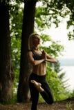 Beau yoga faisant blond dans un tir de parc d'été Photo stock