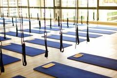 Beaucoup équipement aérien d'exercice de yoga avec les coussins bleus dans le gymnase FO images stock