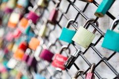 Beaucoup aiment des cadenas sur le concept de barrière avec le foyer sélectif sur une serrure blanche au premier plan Photographie stock libre de droits