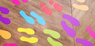 Beaucoup autocollant coloré d'empreinte de pas sur le plancher en bois images stock
