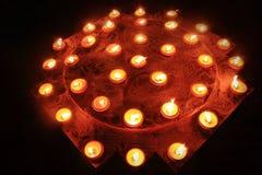 Beaucoup bougies brûlantes sur le fond noir Photographie stock libre de droits