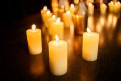 Beaucoup bougies brûlantes sur un fond reflété Photographie stock