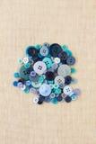 Pile des boutons bleus sur la toile de jute Photo libre de droits