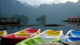 Beaucoup canoë coloré devant la station de vacances de radeau Image libre de droits