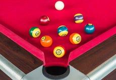 Beaucoup coincent des boules ou des boules de piscine près du trou faisant le coin sur la table rouge Photo stock