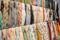 Beaucoup d'écharpes femelles lumineuses et châle Écharpes colorées accrochant sur le marché Les vêtements étirent avec une sélect photos stock