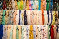 Beaucoup d'écharpes femelles lumineuses et châle Écharpes colorées accrochant sur le marché Les vêtements étirent avec une sélect photo libre de droits