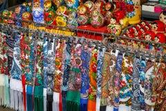 Beaucoup d'écharpes multicolores de tissu et de poupées peintes - matryoshkas, soi-disant souvenirs russes, mensonge sur le compt photos stock
