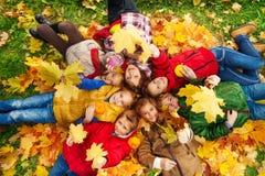 Beaucoup d'amis étendus sur l'au sol d'automne Photographie stock libre de droits