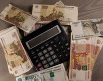 Beaucoup d'argent et calculatrice russes sur un fond en bois Images libres de droits