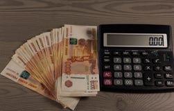 Beaucoup d'argent et calculatrice russes sur un fond en bois Photos stock