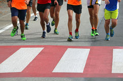 Beaucoup d'athlètes de marathon courent rapidement au-dessus du passage pour piétons dedans Photo stock
