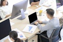 Beaucoup d'employés asiatiques sont attentifs sur travailler avec les ordinateurs modernes photographie stock