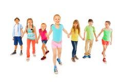 Beaucoup d'enfants avec la petite fille heureuse tiennent des mains Image stock