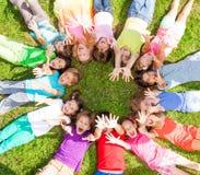 Beaucoup d'enfants avec les mains de levage sur l'herbe Image stock