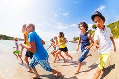 Beaucoup d'enfants ayant l'amusement emballant sur la plage ensoleillée Image stock