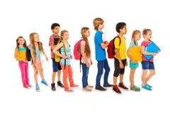 Beaucoup d'enfants heureux dans une ligne à l'école photographie stock