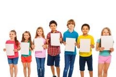 Beaucoup d'enfants se tiennent avec des feuilles de papier blanc dans la ligne Image stock