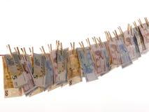 Beaucoup d'euro billets de banque sur une corde à linge Photos stock