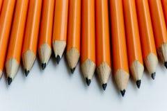Beaucoup d'orange crayonne dans une rangée au-dessus d'une table photographie stock