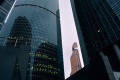 Beaucoup de bâtiments du centre d'affaires de Moscou, du fond jusqu'au dessus, ont découpé le support vert sous un ciel blanc Photos libres de droits