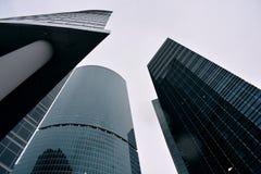 Beaucoup de bâtiments du centre d'affaires de Moscou, du fond jusqu'au dessus, ont découpé le support vert sous un ciel blanc Photographie stock