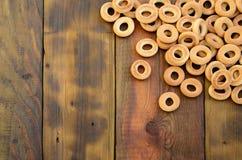 Beaucoup de bagels jaunes frais se trouvent sur la surface du vieux bois foncé Un genre populaire de produits de farine Un de Rus Image libre de droits