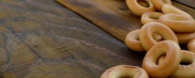 Beaucoup de bagels jaunes frais se trouvent sur la surface du vieux bois foncé Un genre populaire de produits de farine Un de Rus Photo libre de droits