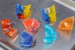 Beaucoup de bagues dentaires ou d'arrêtoirs colorés pour des dents sur le fond de metall Photographie stock