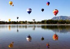Beaucoup de ballons à air chauds volant au-dessus d'un lac mountain Photographie stock libre de droits