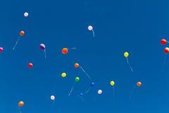 Beaucoup de baloons lumineux dans le ciel bleu Image libre de droits