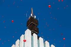 Beaucoup de baloons rouges dans le ciel bleu près du gratte-ciel Photographie stock libre de droits