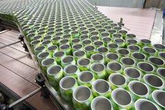 Beaucoup de boîtes vertes ouvertes pour des boissons se déplacent sur le convoyeur photographie stock libre de droits