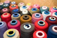 Beaucoup de bobines des fils se tenant sur la table Photo stock