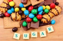 Beaucoup de bonbons avec du sucre de mot sur la surface en bois, nourriture malsaine Images stock