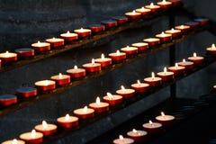 Beaucoup de bougies de cire allumées par vieux fidèle Image libre de droits