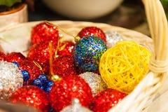 Beaucoup de boules colorées de Noël à un arrière-plan coloré de Noël de panier Image libre de droits