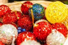 Beaucoup de boules colorées de Noël à un arrière-plan coloré de Noël de panier Images stock