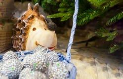 Beaucoup de boules colorées de Noël dans un panier et sous le fond coloré de Noël de hérisson d'arbre Image libre de droits