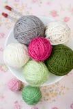 Beaucoup de boules du tricotage sur le fond d'une fleur rose Image stock