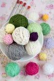 Beaucoup de boules du tricotage sur le fond d'une fleur rose Photo libre de droits