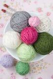 Beaucoup de boules du tricotage sur le fond d'une fleur rose Photos stock