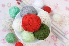 Beaucoup de boules du tricotage sur le fond d'une fleur rose Photographie stock