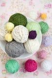 Beaucoup de boules du tricotage sur le fond d'une fleur rose Photo stock