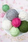 Beaucoup de boules du tricotage sur le fond d'une fleur rose Images libres de droits