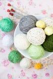 Beaucoup de boules du tricotage sur le fond d'une fleur rose Photographie stock libre de droits